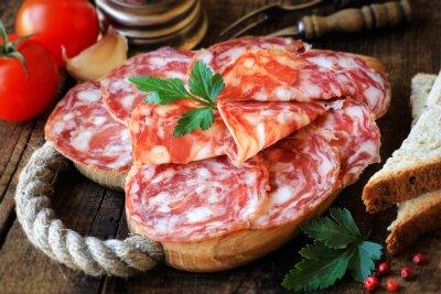 Quadro tapas spagnole - salame affettato sulla scheda di taglio di legno rustico con pane e pomodoro