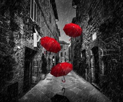 Quadro Umrbellas volanti con vento e pioggia sulla strada buia in una vecchia città italiane in Toscana, Italia