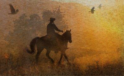 Quadro Un disegno drammatico di un cowboy e il suo cavallo in un prato verso il tramonto con i corvi che volano sopra. Un pezzo tecnica mista di opere d'arte in fotografia e acquerello.