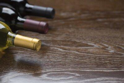 Quadro Varie bottiglie di vino su riflettente legno superficie astratta