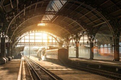Quadro Vecchia stazione ferroviaria con un treno e una locomotiva sulla piattaforma in attesa di partenza. Raggi del sole della sera in archi di fumo.