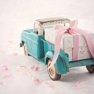 Quadro Vecchio camion giocattolo antico portando una scatola regalo con nastro rosa