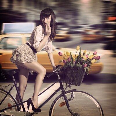 Quadro vintage donna in bicicletta in una strada cittadina con il taxi
