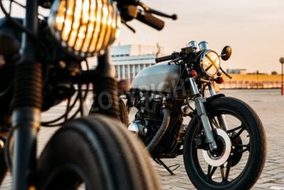 Quadro Vintage moto custom Cafè Racer moto con spia accesa. Uno con griglia faro un'altra con croce nastro sopra ottica a vuoto parcheggio sul tetto durante il tramonto. stile di vita Hipster.