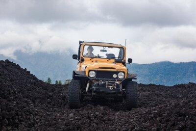 Quadro Vista frontale di un pilota ricci capelli in yelow offroad veicolo parcheggiato in cima a una valle con roccia vulcanica e le montagne a Bali, Indonesia