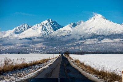Quadro Winter Driving - Winter Road Paese strada conduce attraverso un paesaggio montano invernale.